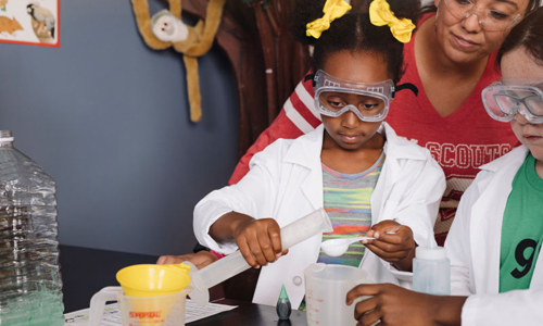 Young girl pouring liquid from graduated cylinder